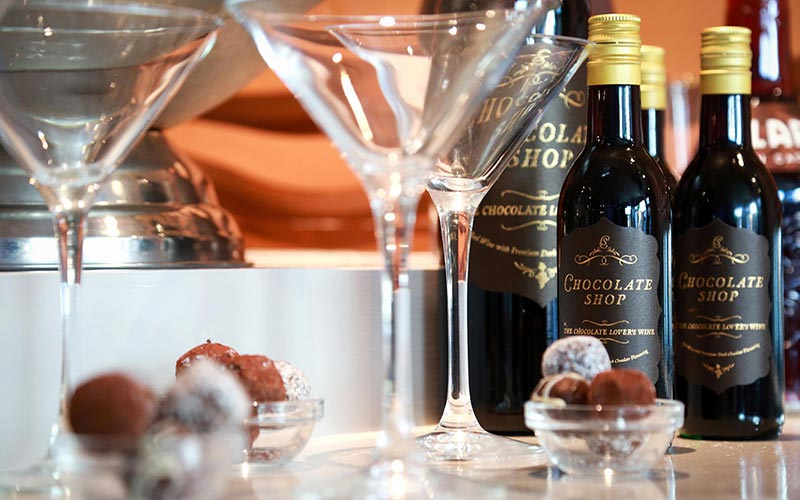 Some chocolate shop wine with cocktail flutes and truffles in the foreground