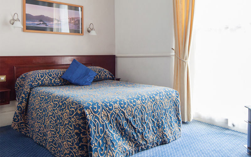A blue double bed in a hotel room
