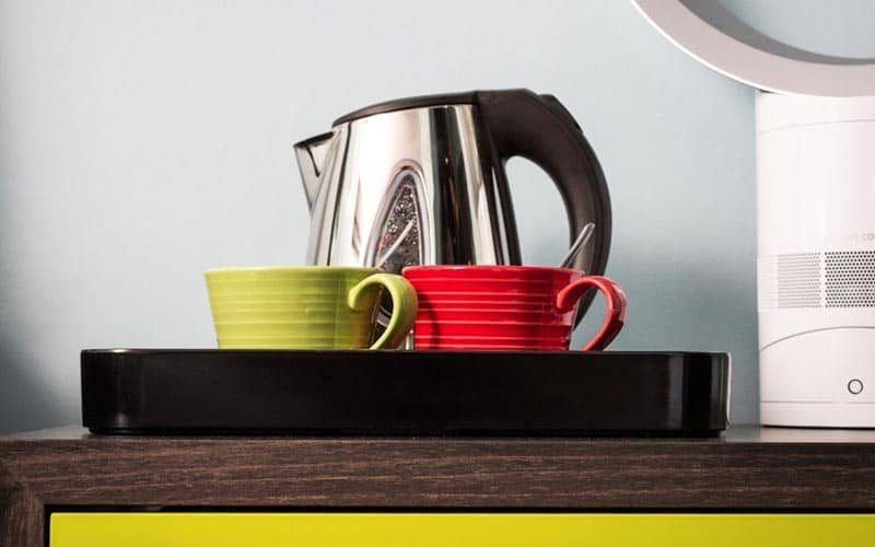 A kettle, red mug and green mug on a black tray on a table