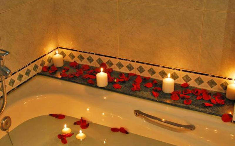 A bathtub lined with rose petals and lit candles