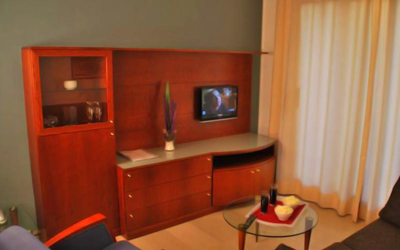 A TV storage unit in a hotel room, with a sofa and coffee table in the foreground