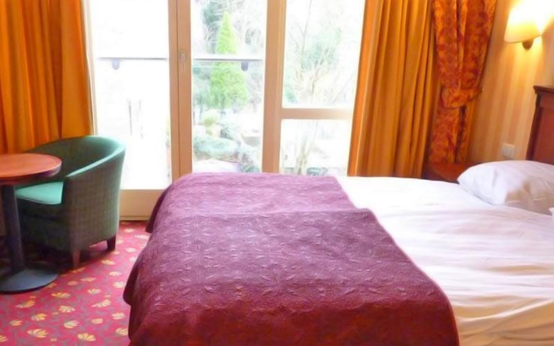 A double bed in a hotel room, with a chair and table in the corner