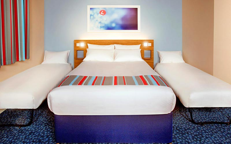 A king size bed, with single beds on either side, in a Travelodge hotel room