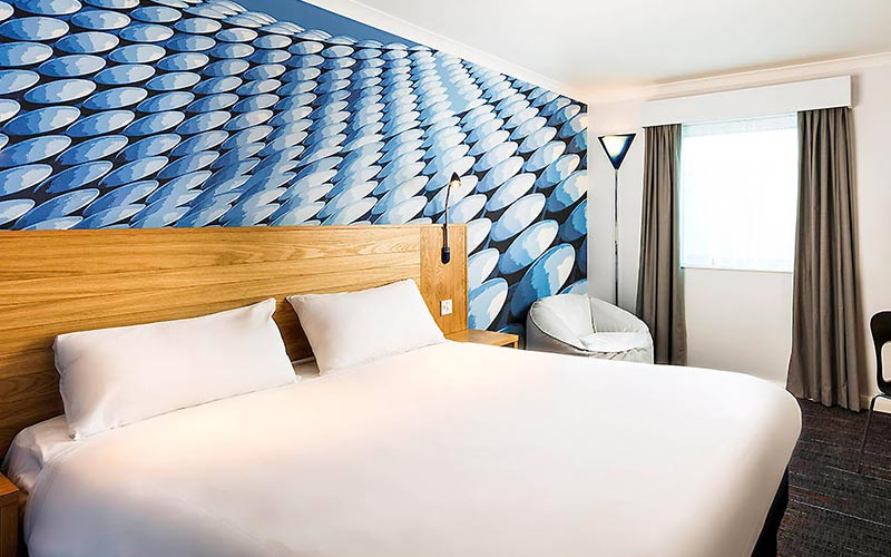 A double room with blue circles on the wall behind the bed