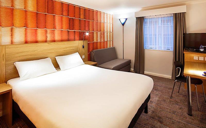A double room with an orange colour scheme in Ibis Styles Birmingham City Centre