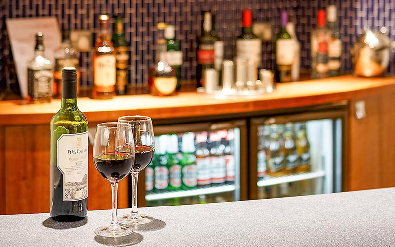 Two glasses of wine and a bottle on the bar of Ibis Styles Birmingham City Centre