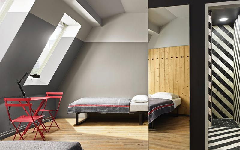 A grey and red themed room with a desk and beds in it