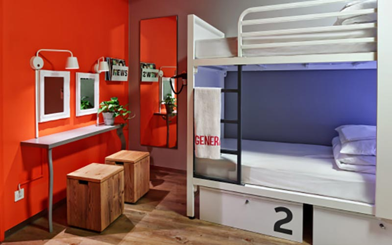 A blue and red room with mirrors, bunk beds and wooden stools