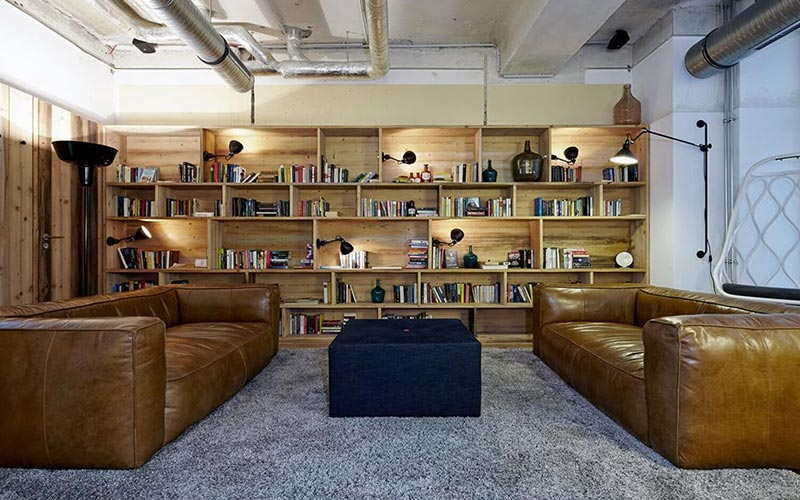 A room with lots of books on shelves and brown leather sofas to chill out on