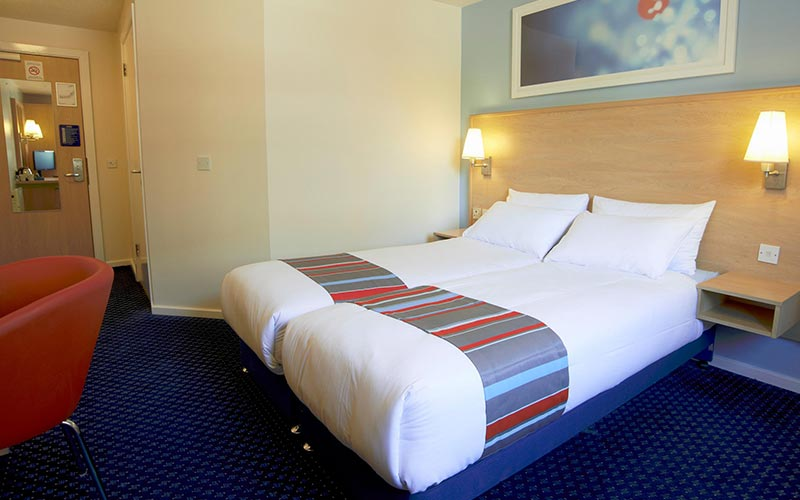 A twin room in Travelodge Cardiff Central with a blue carpet and two lamps mounted on the wall