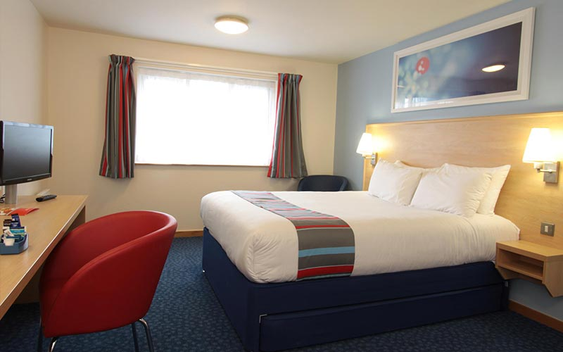 A double room in Travelodge Cardiff Central with a wide window and blue walls and curtains