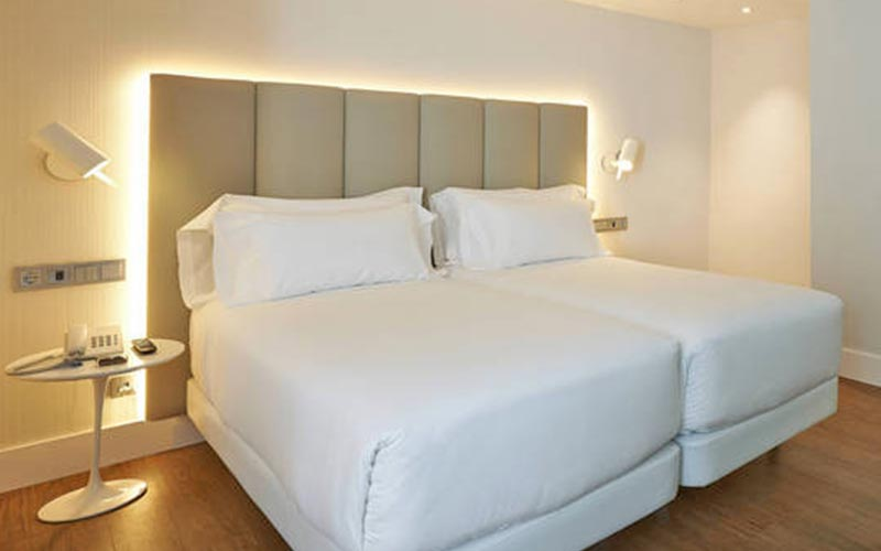 Two double beds, with white bedding, in a hotel room, with a phone on the bedside table