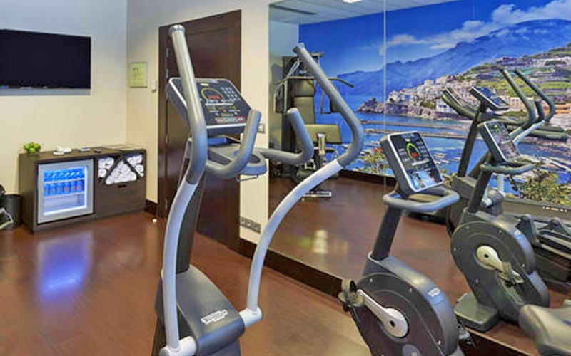 A hotel gym with a plasma TV in the back