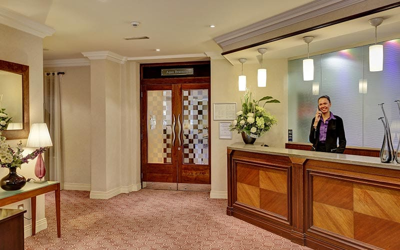 A woman at the wooden reception desk of Best Western Hotel Royale