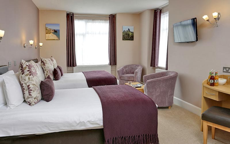 A hotel room with a double and a single bed, topped with throws and cushions, facing two purple chairs and a desk