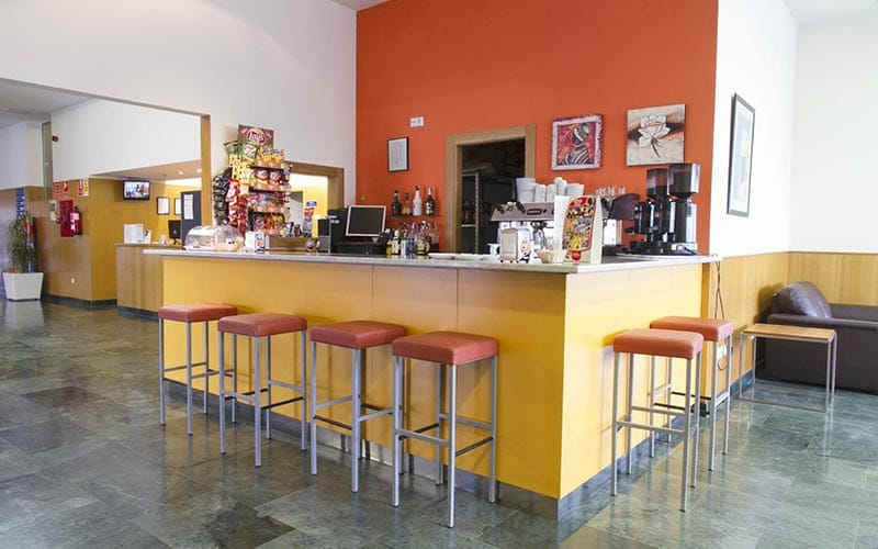 A yellow bar, surrounded by orange bar stools, at Hotel La Estacion