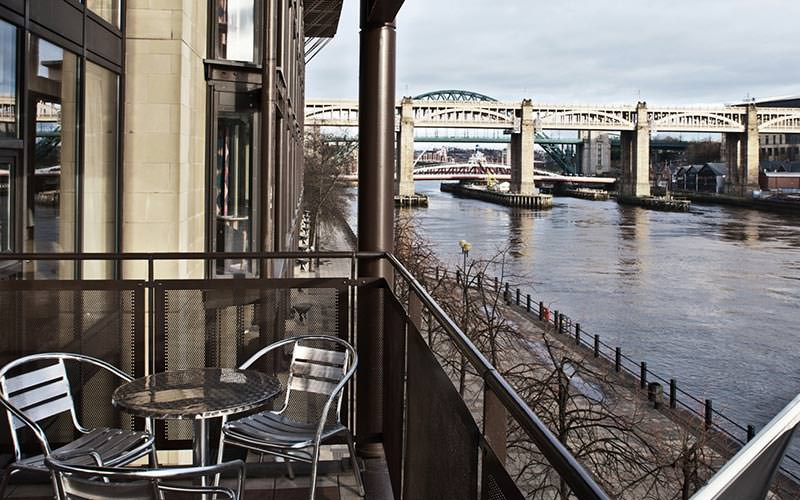 A balcony with two seats looking over the Tyne Bridge