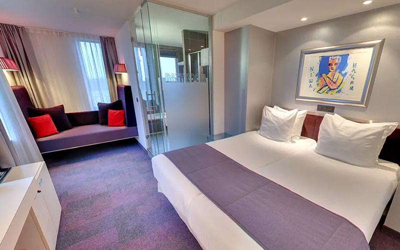 A large hotel room at Westcord Art Hotel, with a double bed, glass bathroom and purple sofa in the background