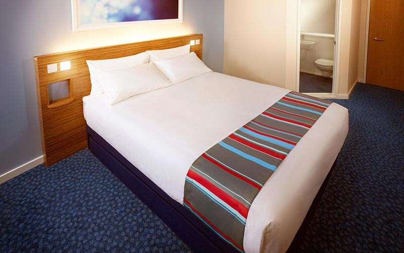 A double bed in a hotel room at Travelodge Birmingham Central Newhall Street