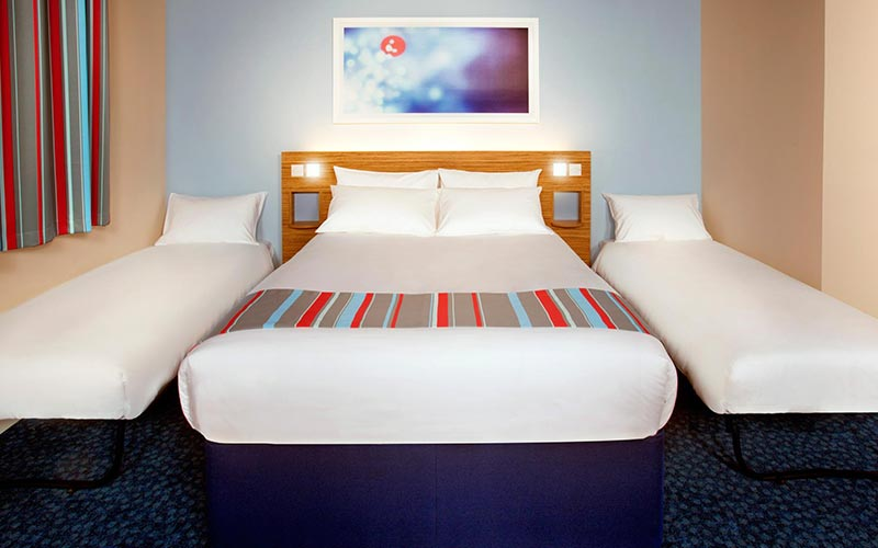 A double bed, with two single beds either side, in a hotel room at Travelodge Birmingham Central Newhall Street
