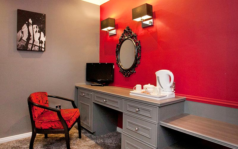 A dressing table against a red wall, with a chair and TV, with a gilded mirror on the wall