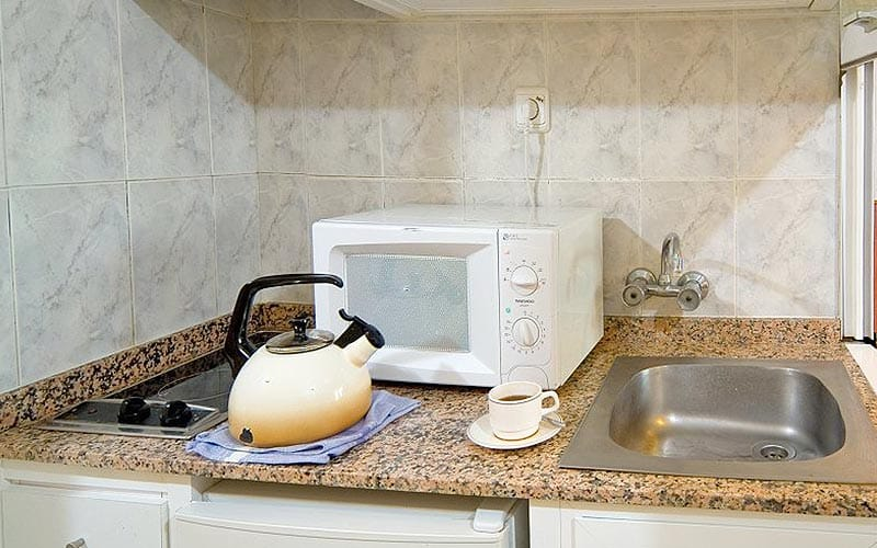 A kettle, microwave and a cup on a kitchen counter