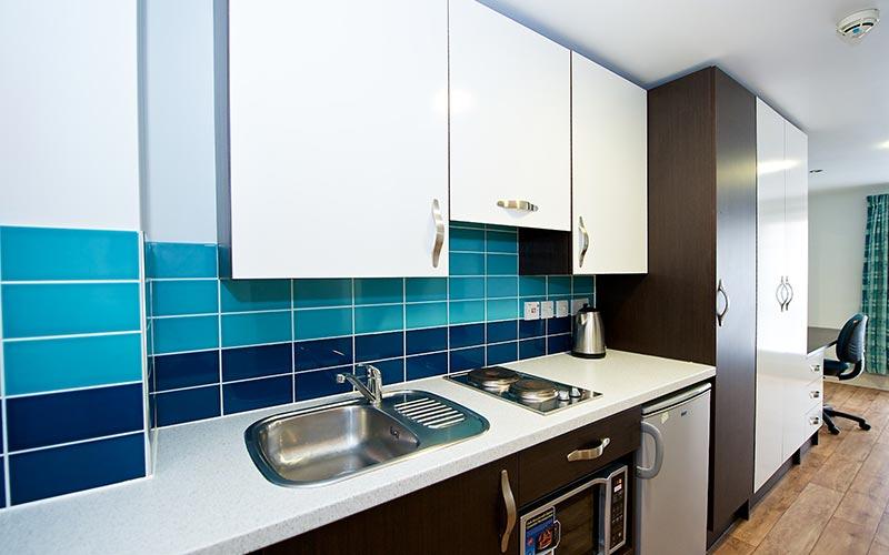 A blue kitchen in a CityLiveIn Apartment
