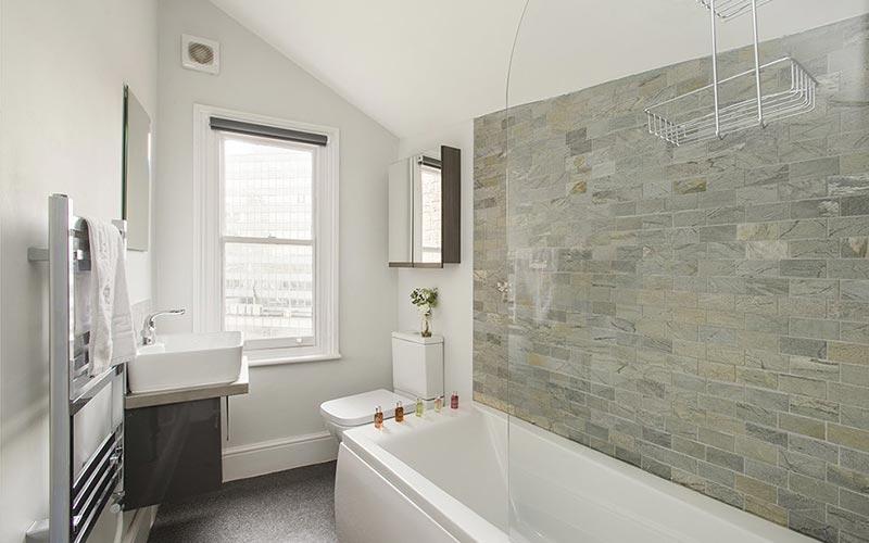 A grey tiled bathroom at Market Street Apartments