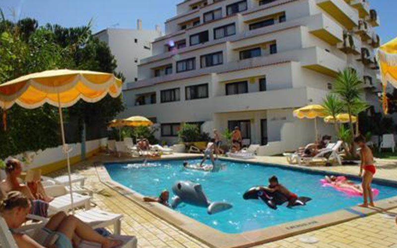 People in and around the outdoor swimming pool at Ourasol Apartamentos Turisticos