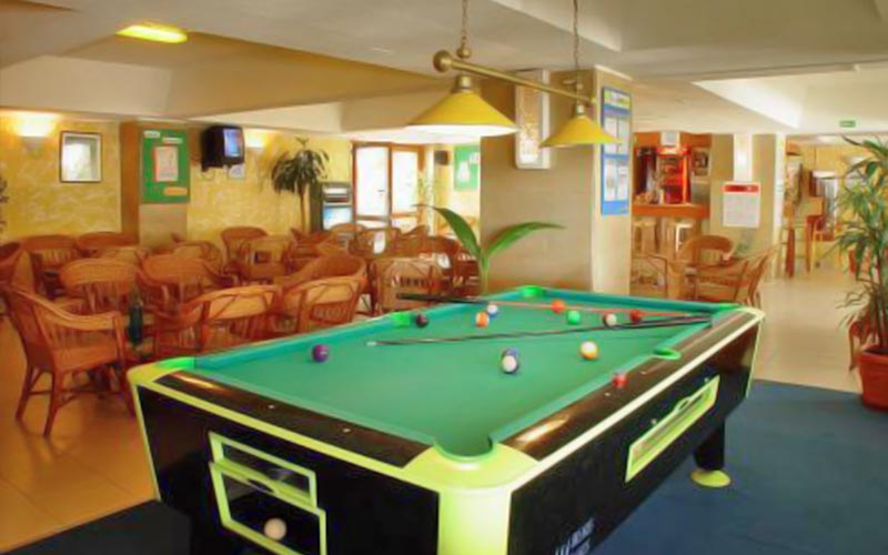 A pool table, with tables and chairs in the background