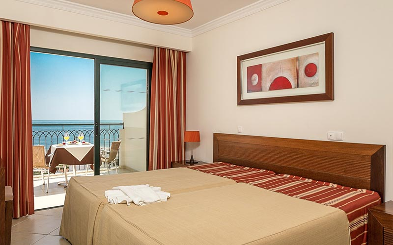 A double bed in a hotel room at Cerro Mar Atlantico, with a balcony in the back