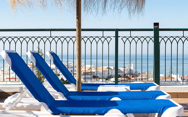 Three blue sunloungers in a line, on the terrace at Cerro Mar Atlantico