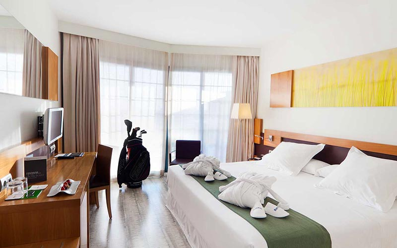 A double bed in a room at Occidental Estepona Hotel & Thalasso Spa, facing a desk with golf clubs in the background