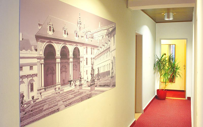 A canvas mounted on the wall in a corridor with a red carpet