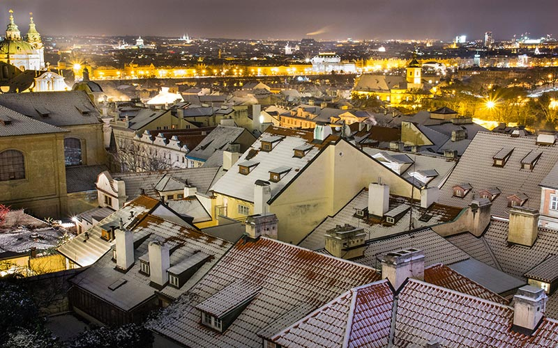 The rooftops of a city at night, with lights twinkling