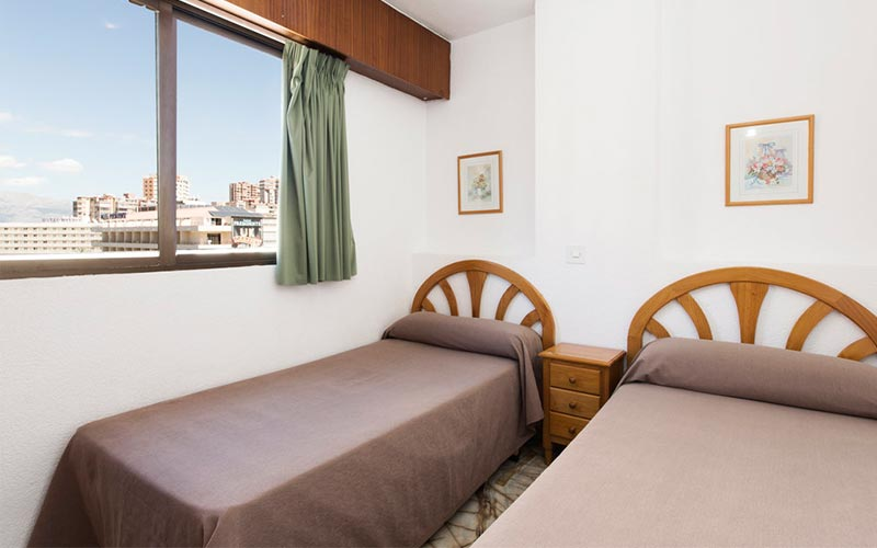 Two beds in a room with a window looking out over Benidorm