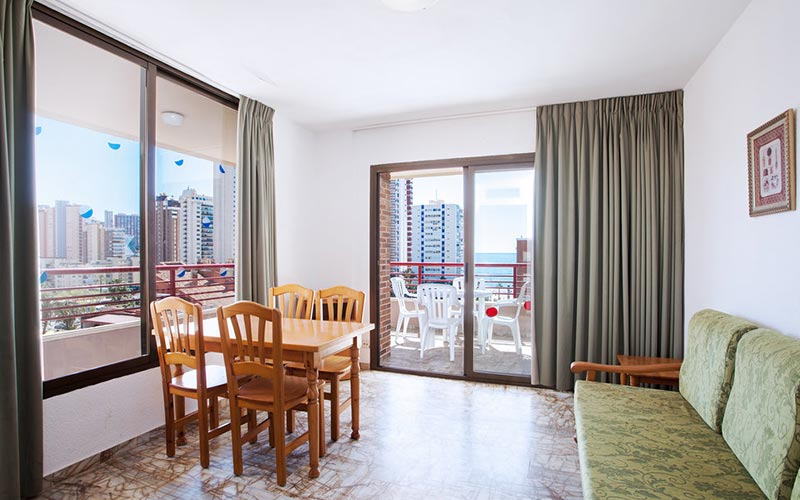A living room in an apartment with a dining table and chairs, and two windows looking out over Benidorm