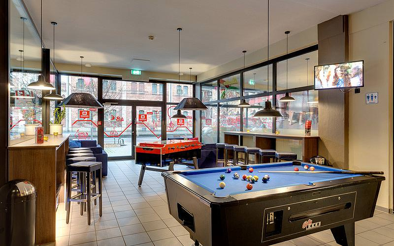 A pool table in the foreground, with table football and stools along the wall in the background