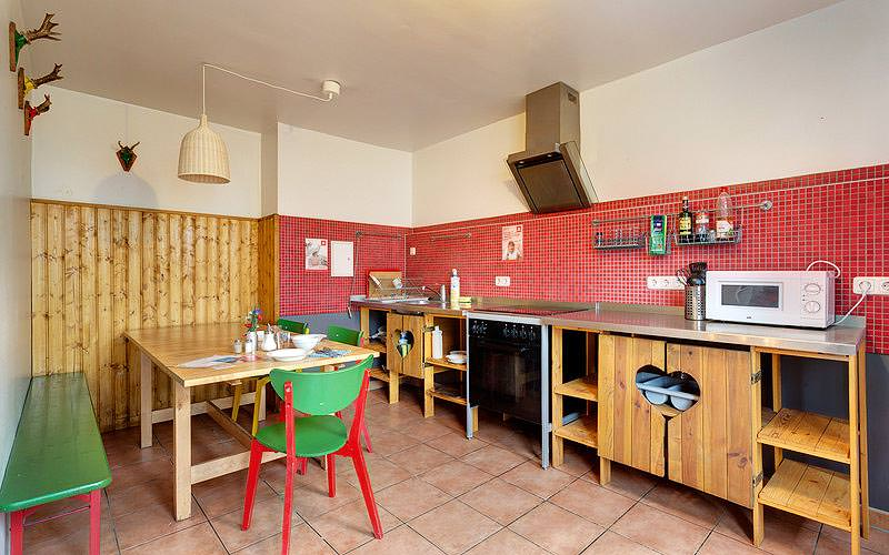 Kitchen appliances along a tiled wall, with tables and chairs in the corner