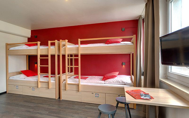 Two wooden bunk beds along a red wall, with a TV and desk in the foreground
