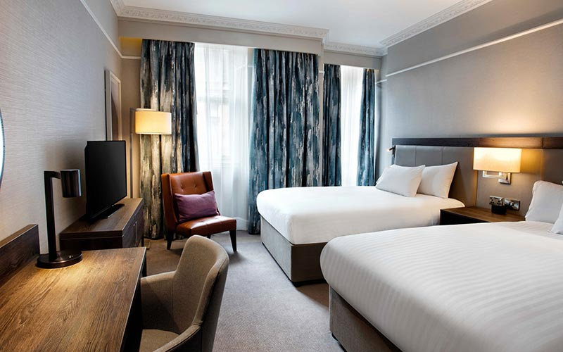Two double beds in a bedroom at Hilton Edinburgh Carlton