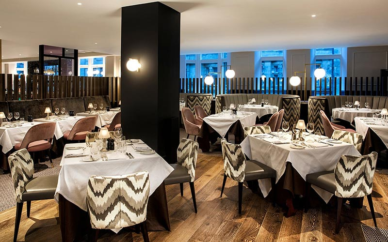 Tables and chairs set for food in the restaurant at Hilton Edinburgh Carlton