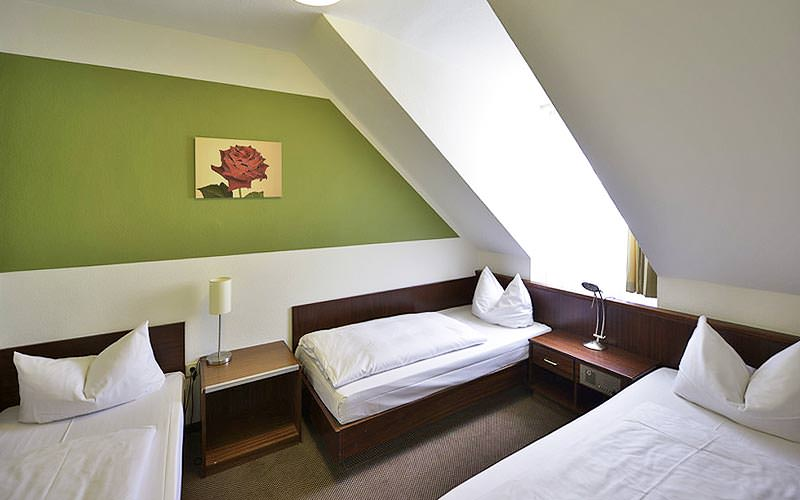 Three single beds along a green wall, with bedside tables between the three of them