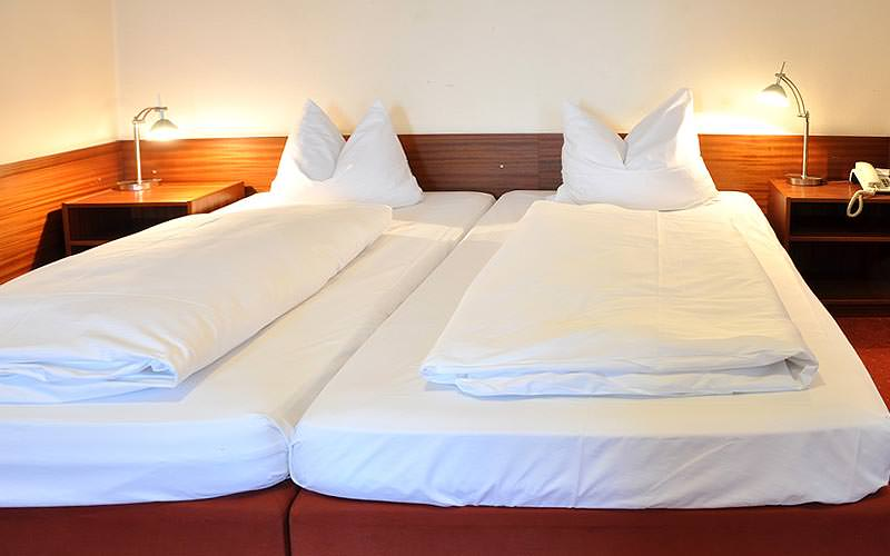 Two white single beds topped with bedding, with bedside tables on each sides of the beds