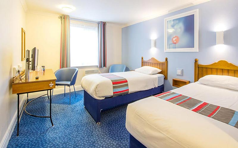 A twin room with a blue carpet and blue and yellow walls