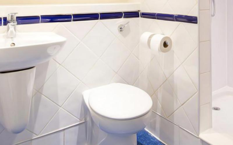 A navy and white bathroom with sink and toilet