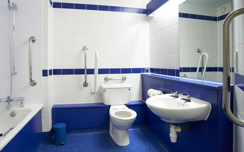A blue and white bathroom with toilet, sink and bath in Travelodge Chester Warrington Road