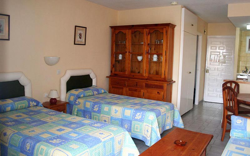 Two single beds with blue bedding in a bedroom at Apartmentos Minerva Jupiter