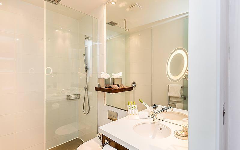 A clean, modern bathroom with an illuminated mirror
