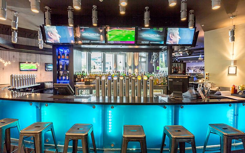 The bar area with football on the TV in the Signature Sandman